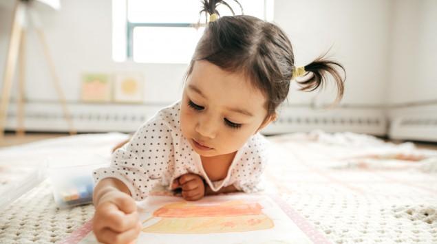 Ein kleines Mädchen malt mit Buntstiften auf einer Decke.