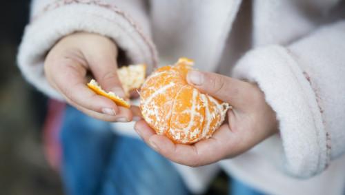 Ein Mädchen schält eine Mandarine