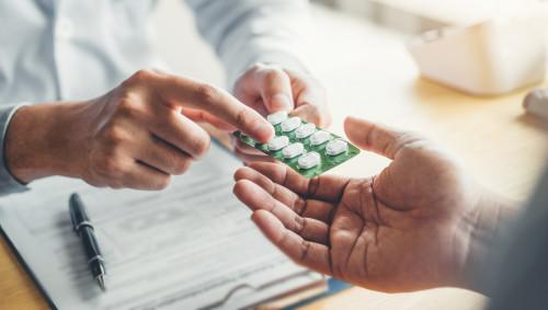 Ein Arzt übergibt einem Mann einen Tabletten-Blister.