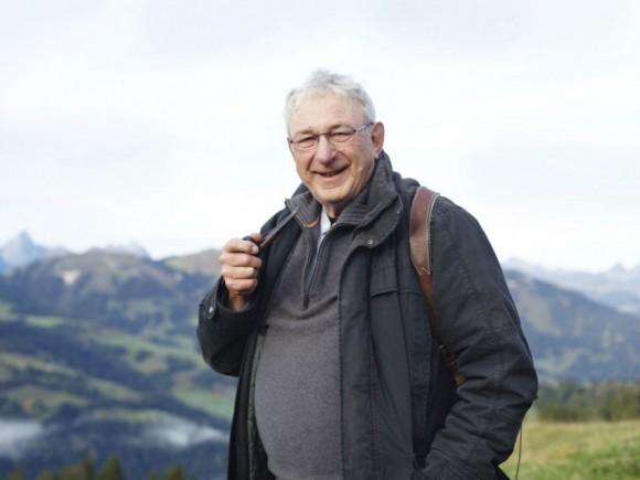Ein leicht übergewichtiger Mann vor einem Bergpanorama.