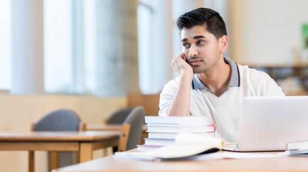 Ein nachdenklich aussehender Mann sitzt am Tisch mit Büchern.