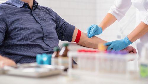 Eine Ärztin nimmt einem Mann Blut ab.