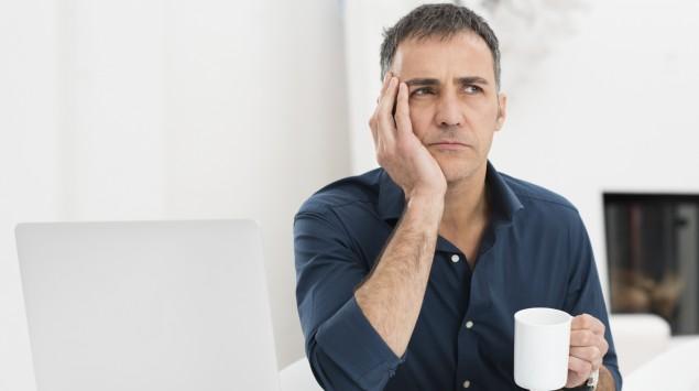 Ein besorgt aussehender Mann im Büro hält eine Kaffeetasse in der Hand.
