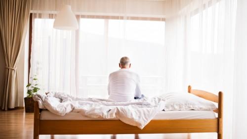 Rückansicht eines Mannes, der auf dem Bett sitzt.