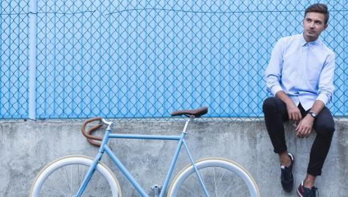 Ein Mann sitzt neben seinem Fahrrad.