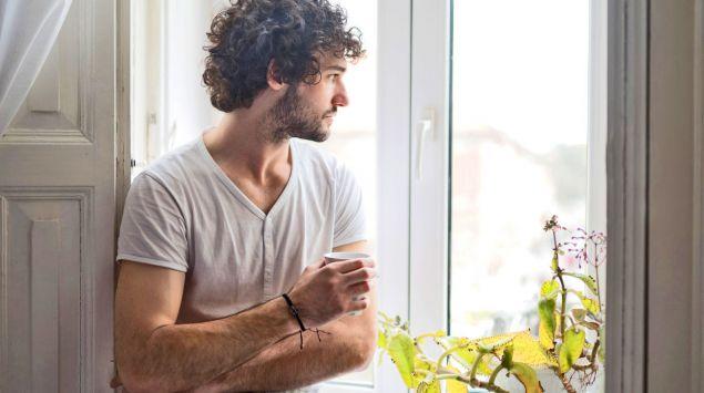 Ein junger Mann schaut aus dem Fenster