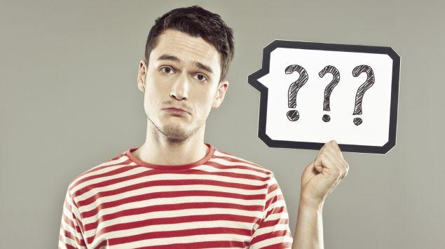 Ein Mann hält ein Schild mit drei Fragezeichen hoch.