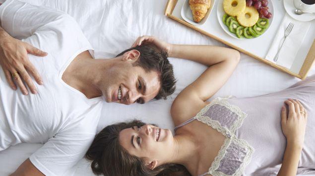 Ein glückliches junges Paar im Bett.