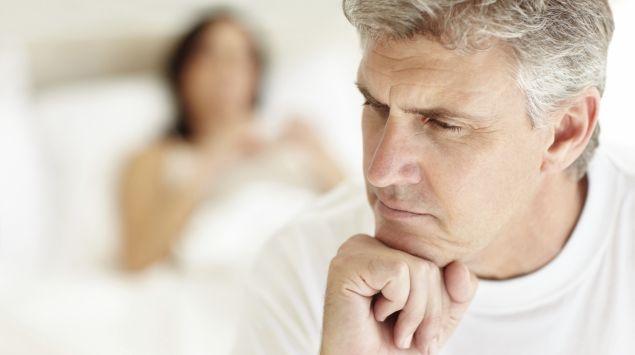 Ein Mann sitzt nachdenklich auf der Bettkante, im Hintergrund liegt eine Frau im Bett.