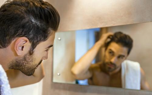 Ein Mann überprüft vorm Spiegel seine Haare.