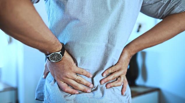 Ein Mann greift sich mit beiden Händen ins Kreuz.