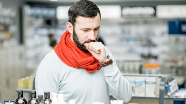 Ein Mann steht in der Apotheke und hustet.