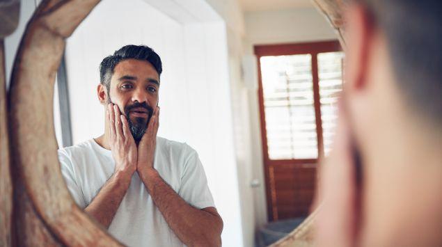 Ein Mann schaut in den Spiegel.