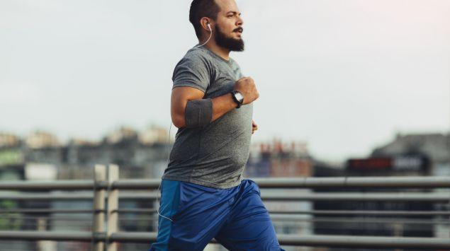 Ein leicht übergewichtiger Mann joggt über eine Brücke.