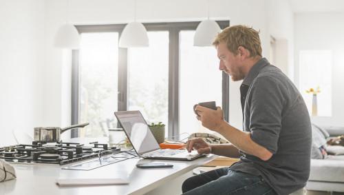 Ein Mann sitzt am Küchentisch und arbeitet am Laptop.