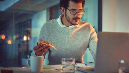 Ein Mann sitzt spätabends am Laptop und hält ein Stück Pizza in der Hand.