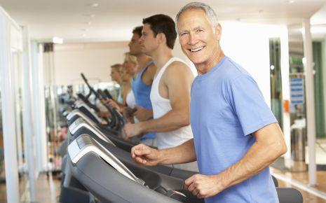 Ein älterer Mann neben anderen Männern auf dem Laufband.