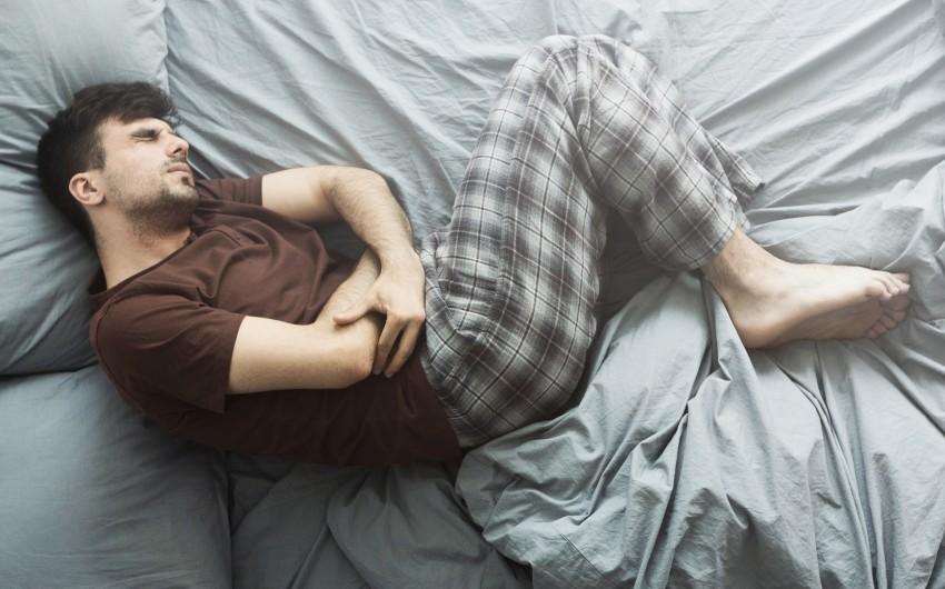 Bauchspeicheldrüsenentzündung: Ein Mann liegt mit starken Bauchschmerzen im Bett und hat eine Schonhaltung mit angezogenen Beinen eingenommen.