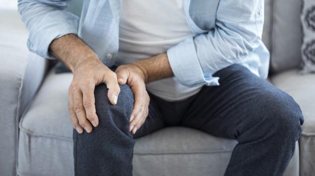 Ein Mann sitzt auf einem Sofa und greift sich ans schmerzende Knie.