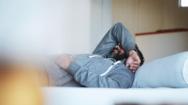 Ein Mann liegt auf dem Bett und hat einen Arm über die Augen gelegt.