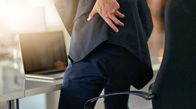 Das Bild zeigt einen Mann mit Jacket, der sich den Rücken hält.