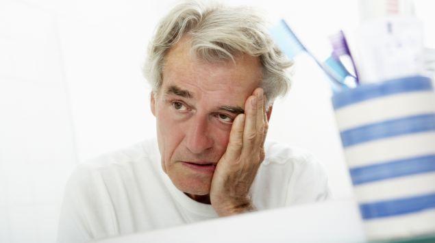 Ein älterer Mann schaut müde in den Spiegel.