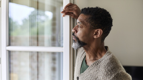 Ein Mann dunkler Hautfarbe schaut nachdenklich aus dem Fenster.