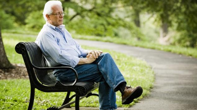 Ein älterer Mann sitzt auf einer Parkbank.