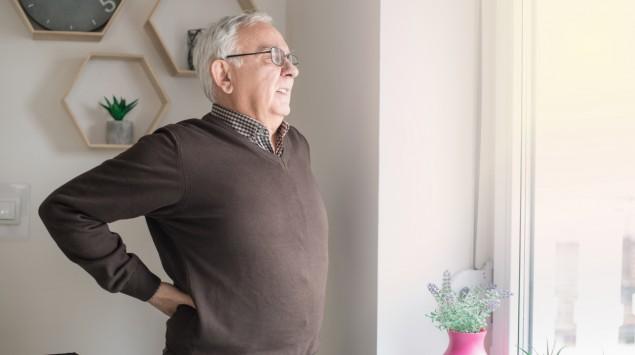 Ein älterer Mann fasst sich an den Rücken.
