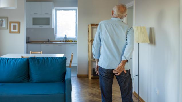 Rückansicht eines Seniors, der sich an das Gesäß fasst: In bestimmten Fällen ist bei vergrößerten Hämorrhoiden eine OP nötig.