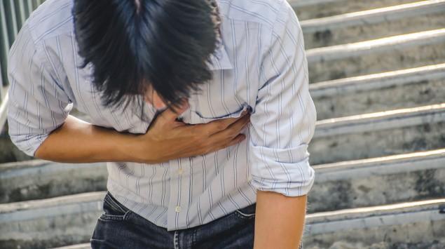 Rippenbruch: Ein Mann steht an einer Treppe und hät sich vorgebeugt die Hand an den schmerzenden Brustkorb.