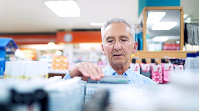 Ein älterer Mann kauft Shampoo.