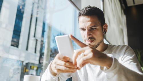 Ein Mann schaut mit ernstem Gesicht auf sein Smartphone.