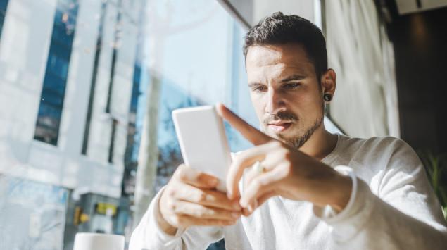 Ein Mann blickt mit ernstem Gesichtsausdruck auf sein Smartphone.