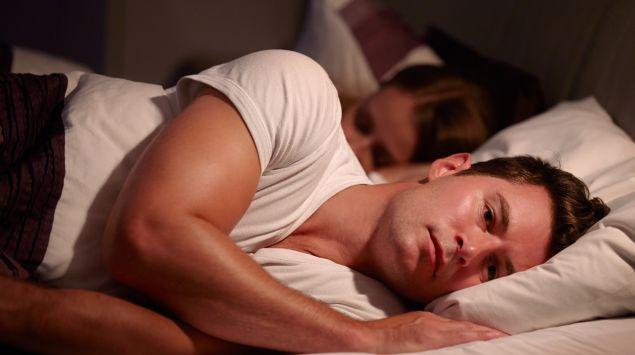 Ein Mann liegt neben seiner Partnerin im Bett.