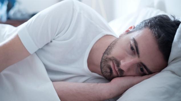 Ein Mann liegt im Bett.