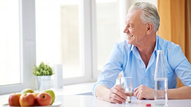 Ein Mann sitzt am Tisch und trinkt Wasser.