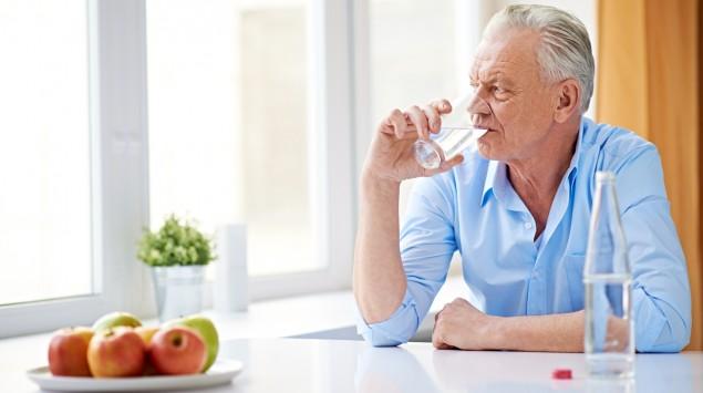 Ein Mann trinkt Wasser und schaut missmutig aus dem Fenster.