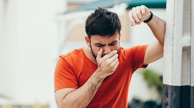 Ein Mann hält sich die Hand vor den Mund: Bluterbrechen bezeichnen Ärzte als Hämatemesis.