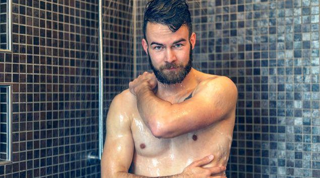 Ein Mann steht unter der Dusche.