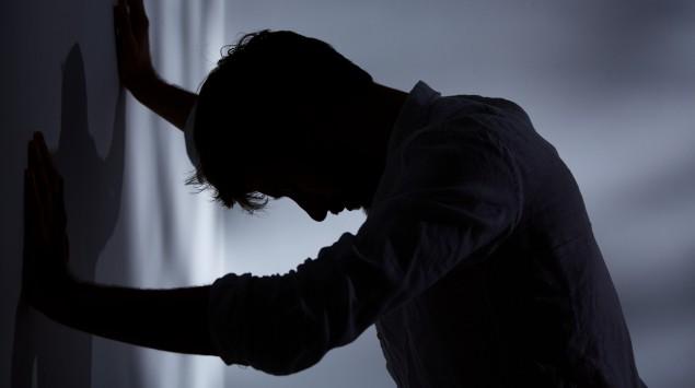 Ein Mann stützt sich an der Wand ab und lässt den Kopf hängen.