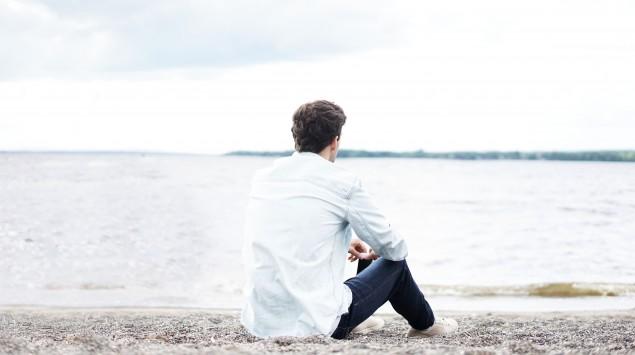 Das Bild zeigt einen jungen Mann, der an einem See sitzt.