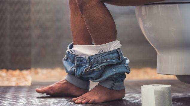 Das Bild zeigt einen Mann, der auf einer Toilette sitzt.