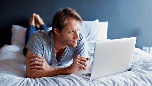 Das Bild zeigt einen Mann, der auf dem Bett liegt und auf seinen Laptop schaut.