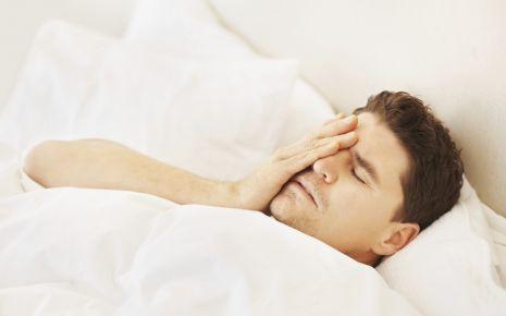 Morbus Meniére: Ein Mann liegt im Bett und fasst sich an den Kopf.