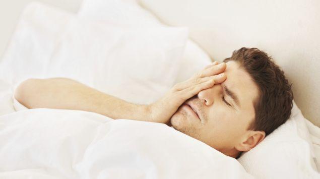 Ein Mann liegt im Bett und fasst sich an den Kopf.