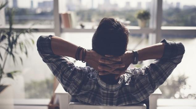 Ein verschränkt entspannt die Arme hinter dem Kopf.