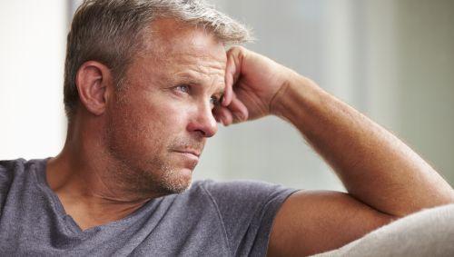 Ein Mann mittleren Alters sitzt mit grüblerischer Miene auf einem Sofa, den Kopf auf den Arm gestützt.