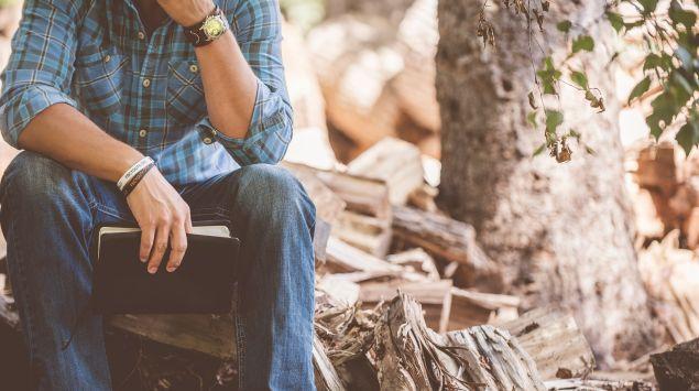 Das Bild zeigt einen Mann, der im Wald sitzt.
