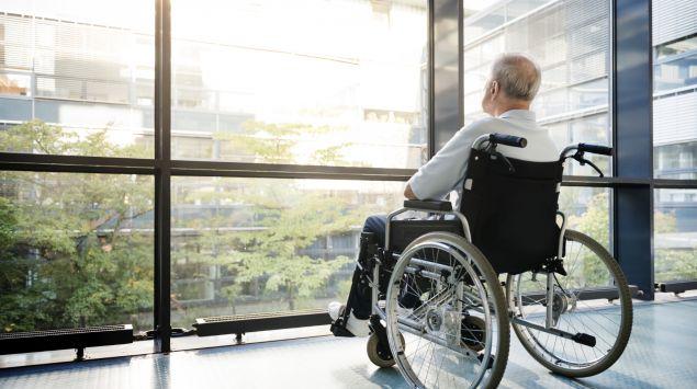 Das Bild zeigt einen älteren Mann im Rollstuhl
